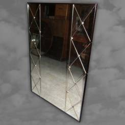 A mirror with geometric design and circular chrome studs
